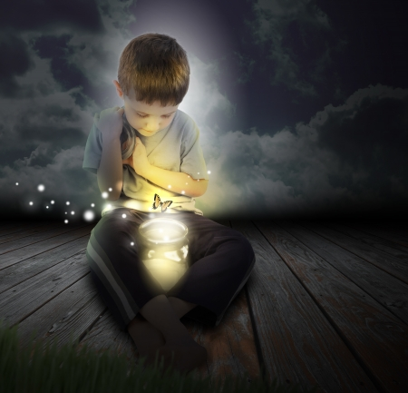 A boy is looking at a glowing bug firefly coming out of a jar with a butterfly at night
