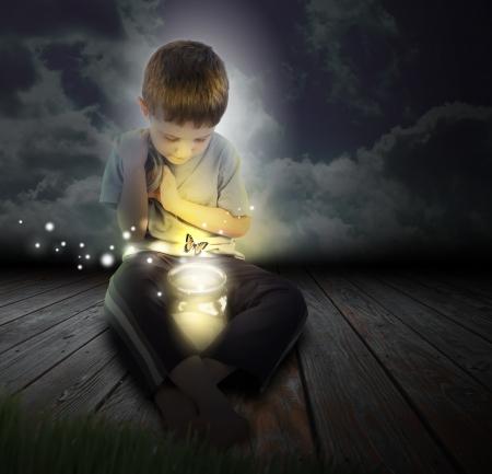 Een jongen is op zoek naar een gloeiende bug vuurvlieg die uit een pot met een vlinder in de nacht Stockfoto