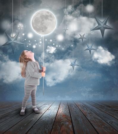 꿈의 개념 구름과 푸른 하늘에서 별을 가진 문자열에 풍선 달 밤에 노는 어린 소녀. 스톡 콘텐츠