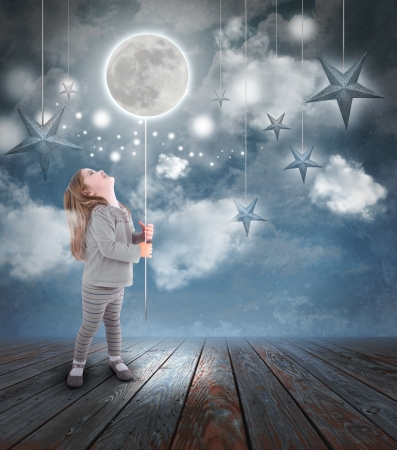 Young little girl playing at night with a balloon moon on a string with stars in the blue sky with clouds for a dream concept.