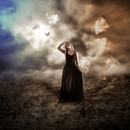 A young woman is wearing a black dress in a dark dry, nature landscape with a butterfly flying up to represent hope  photo