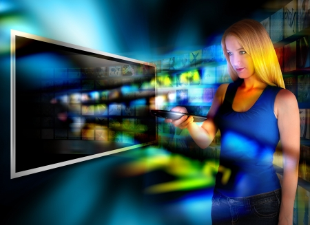 A person is holding a remote control and watching television on a widescreen tv with video images coming out on a black background  Фото со стока