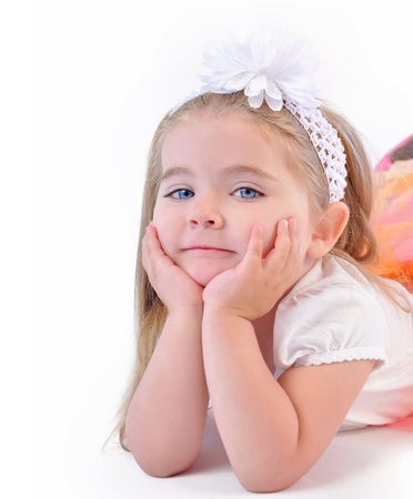 A young little girl is laying down with her hands to her face thinking  She is wearing a nice outfit on an isolated white background  Stock Photo - 20674893