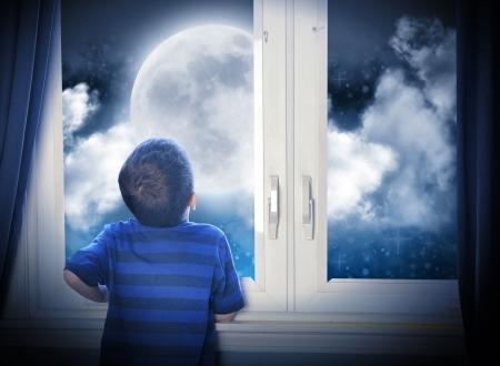 universum: Ein kleiner Junge schaut aus dem Fenster auf einem großen Mond in der dunklen Nacht mit Sternen und Platz für ein Astronomie oder imagaination Konzept