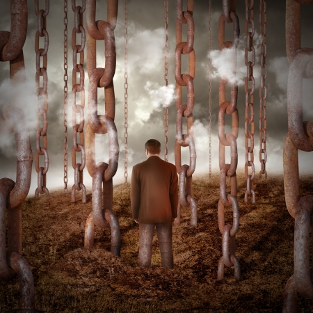 A lonely sad man is chained to the dry landscape with other chains going into the sky for a power or freedom concept. photo