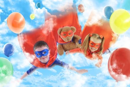 super human: Dos ni�os peque�os superh�roes est�n volando en el cielo con globos y un osito de peluche para una fiesta o concepto de rescate.