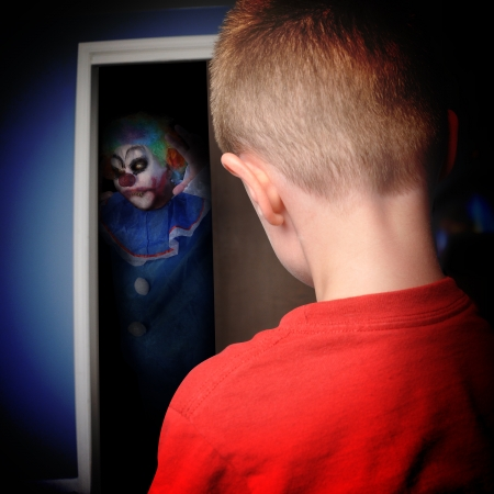 A scary clown is coming out of a boys closet in his bedroom at night for a nightmare or scary concept  Stock Photo