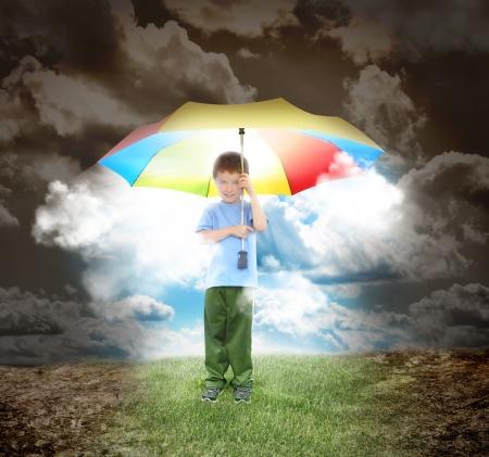 Een jong kind houdt een regenboog paraplu met zon gloeit op De jongen is omgeven met een opgedroogde landcsape en gras onder zijn schoenen voor een home concept Stockfoto