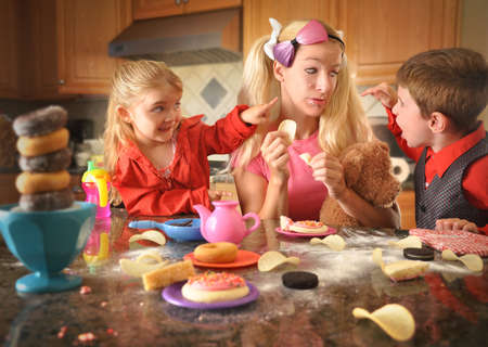 children acting: A mother is acting like a child and eating lots of junk food while her children are upset with her  There is a mess of chips, donuts and cookies
