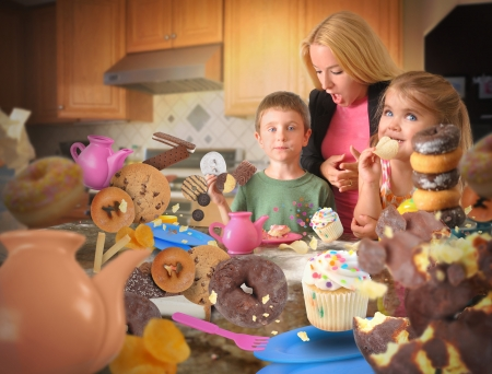 Two children are eating messy junk food snacks such as cookies, donuts and cupcakes in the kitchen with an angry mother