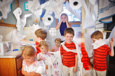 A mother is shocked and full of stress while the children make a mess in the bathroom with toilet paper  photo