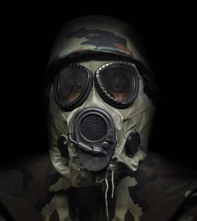A soldier is wearing a gas mask on a black isolated background for a war defense concept  Standard-Bild