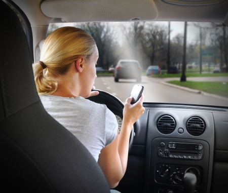A young woman  is on the cell phone textign and driving with a road in the windshield for an danger or distracted driving concept