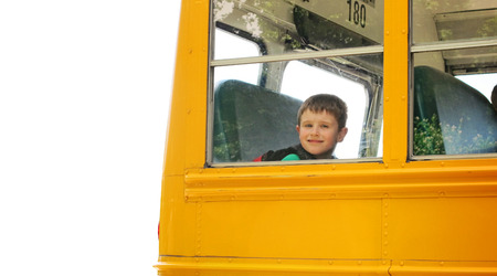 school schedule: A young boy is on a yellow school school bus on a white isolated background for an education concept  Stock Photo
