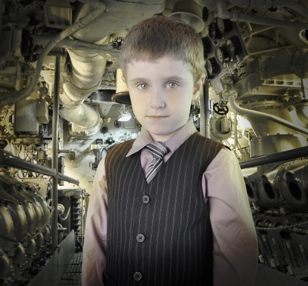 A smart, mature young boy is wearing a suit and tie with a mechanical background behind him for a engineering or science concept Stock Photo - 23130617