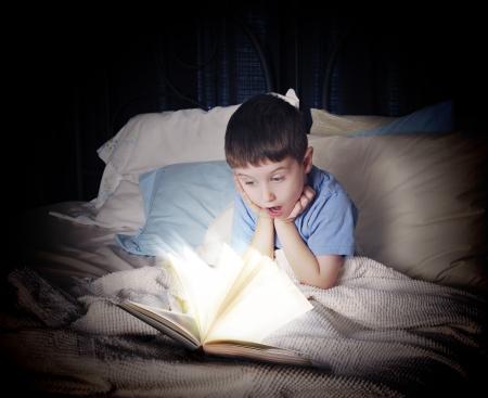 kniha: Malý chlapec je čtení zářící otevřenou knihu o jeho posteli v noci na koncepci fantazii nebo učení Reklamní fotografie