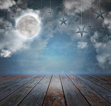 Een maan en sterren zijn in de nachtelijke hemel met hout aan de onderkant copyspacegebied om uw tekstbericht toevoegen.