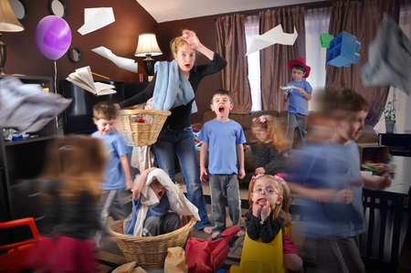 estr�s: Un ama de casa se destac� e intent� tratando de limpiar la casa mientras los ni�os salvajes est�n corriendo haciendo un l�o de un concepto disciplina o con hijos.