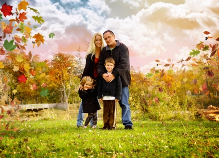 A happy family is standing outside in a park with fall leaves around them and a beautiful sky for a text or copyspace area. photo