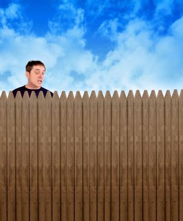 enclosures: Un vicino di casa ficcanaso � guardando oltre un recinto in un cortile a qualcosa di shock e sorpresa sul suo volto per un segreto o riservatezza concetto.