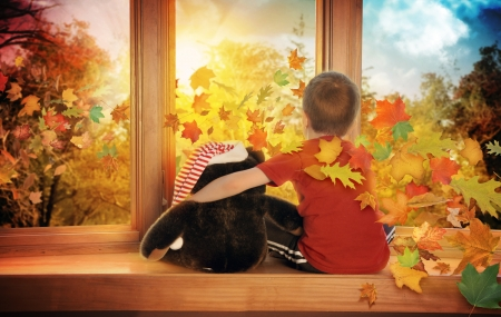 A little boy is sitting by the window watching the sunset as orange leaves blow into the house for a fall season concept. photo