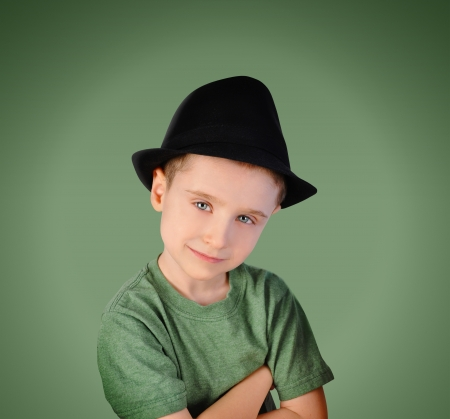 A little kid is wearing a black hat and smiling on a green background. The boy is has a t-shirt and looks like he is thinking for a portrait concept. photo