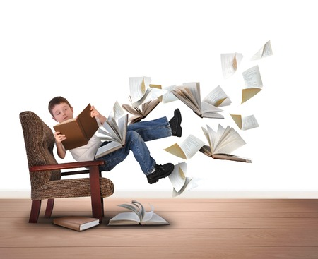 A young boy is reading a book floating in in the air on a white isolated background. There are pieces of paper flying up around him for an education concept.