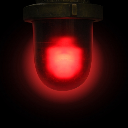 A red flashing siren is on a balck isolated background for a emergency or danger concept  Banco de Imagens