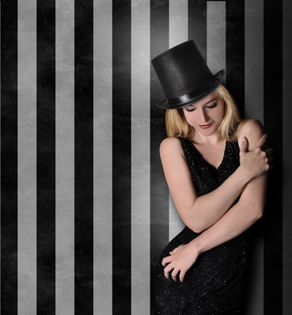 A pretty woman is wearing a top hat and is holding her body Stock Photo - 25438665