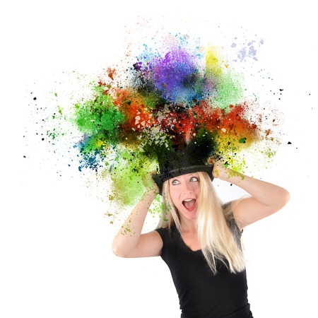 A girl is wearing a black top hat that has rainbow paint splatters coming out of the top on a white isolated