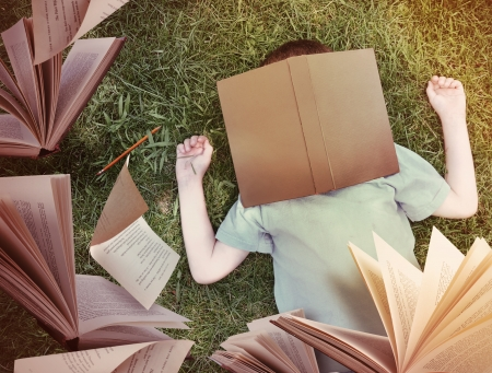 A little boy has fallen asleep on the grass with a brown book on his face. Open books and paper are flying up for an education or story concept. photo