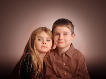 A little boy and girl are posing against a brown background for a family or love concept. The children have blue eyes. Stock Photo - 25296003