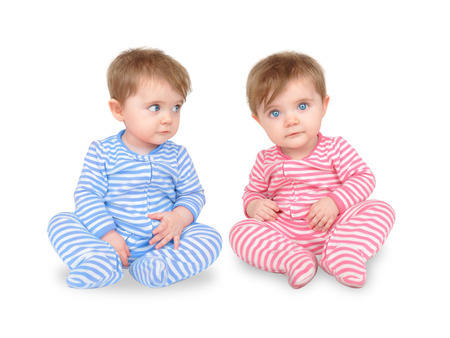 Two identical twins are sitting on a white isolated background.