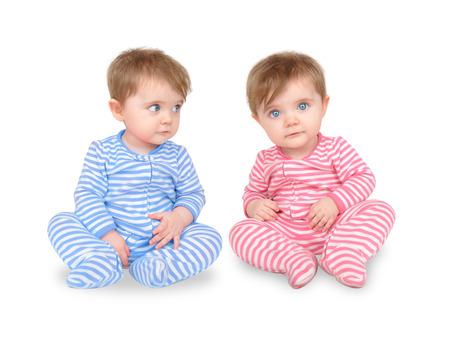 Deux jumeaux identiques sont assis sur un fond blanc isolé. Banque d'images
