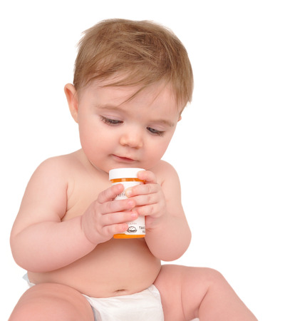 A baby is sitting on the floor on a white background and playing with bottle.