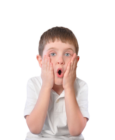 forgetful: A little boy is holding his hands to his face with an open mouth in shock and surprise on a white background for a secret or fear concept