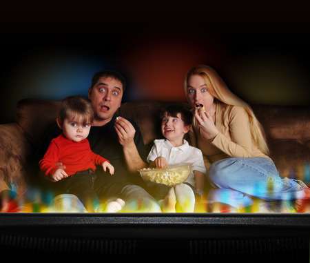 A young family is watching television and having movie night on the couch at home  The background is black and there are 2 children