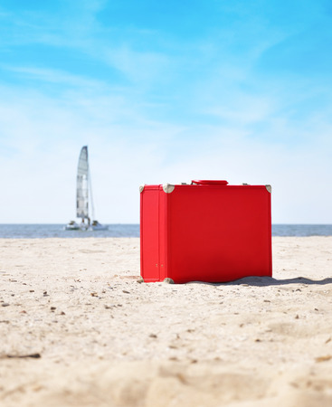 A red suitcase is on the beach with a sailboat in the background on water  There is sand and it is a sunny day  Use it for a vacation or travel concept   photo