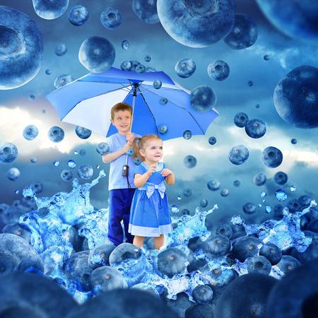 sotto la pioggia: Due bambini sono sotto un ombrello guardando cadere mirtilli per la pioggia Acqua è schizzi per un frutto, dieta o concetto di nutrizione
