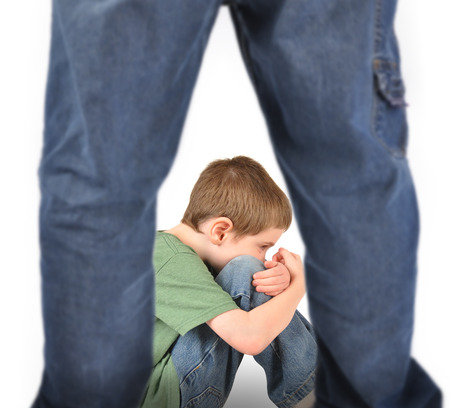 bully: A young boy is sitting on the ground and scared  There are legs in the foreground to represent abuse, fear, or a bully