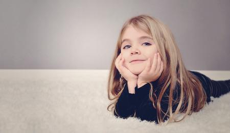 Una niña feliz está sentando en el suelo blanco con área de copyspace para un mensaje de texto Úsalo para una casa o el concepto de familia Foto de archivo