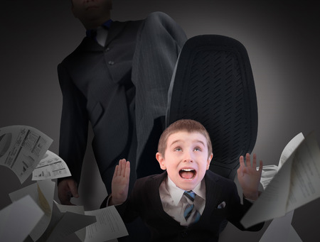 A little business man is under a big bosses foot about to crush or step on him. His hands are in the air scared. photo