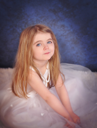 A beautiful little girl is dressed up in a glamorous white dress sitting down on a blue for a fashion or wedding concept. photo