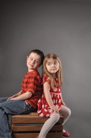 兄と妹の兄弟は箱に座っています。子供たちはお互いに友人か探してコンセプトが大好き。