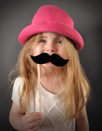 A little child is holding a pretend mustache disguise for a humor or fun concept. The girl is smiling and happy with a pink hat.
