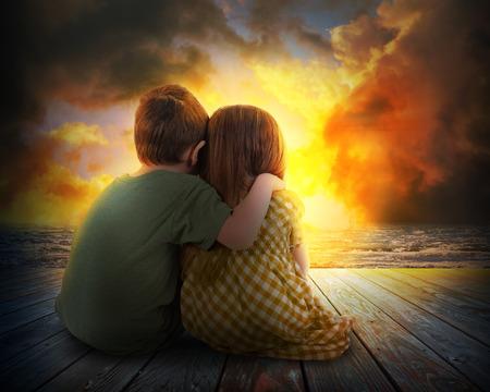 Ein kleiner Junge und Mädchen sind umarmt und beobachten den Sonnenuntergang in den Himmel. Die Kinder sitzen auf Holz für eine Familie, Liebe oder Urlaub Konzept.