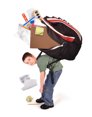 heavy: A young child is standing with a large heavy school book bag on his back for a homwework or stress concept on a white background. Stock Photo