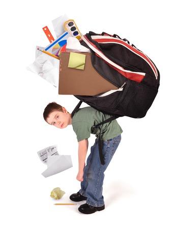Un niño está de pie con una gran bolsa de libros de la escuela pesada en la espalda para una homwework o concepto de la tensión sobre un fondo blanco. Foto de archivo