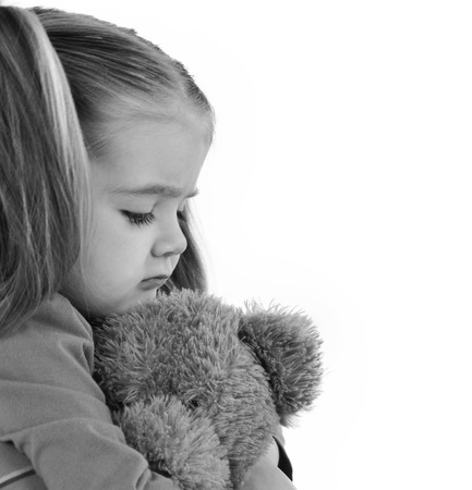 A sad little girl is holding a stuffed teddy bear on a white isolated background for a timeout or emotion concept. photo