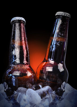 Two cold glass beer bottles are wet with waterdrops on ice with a black isolated
